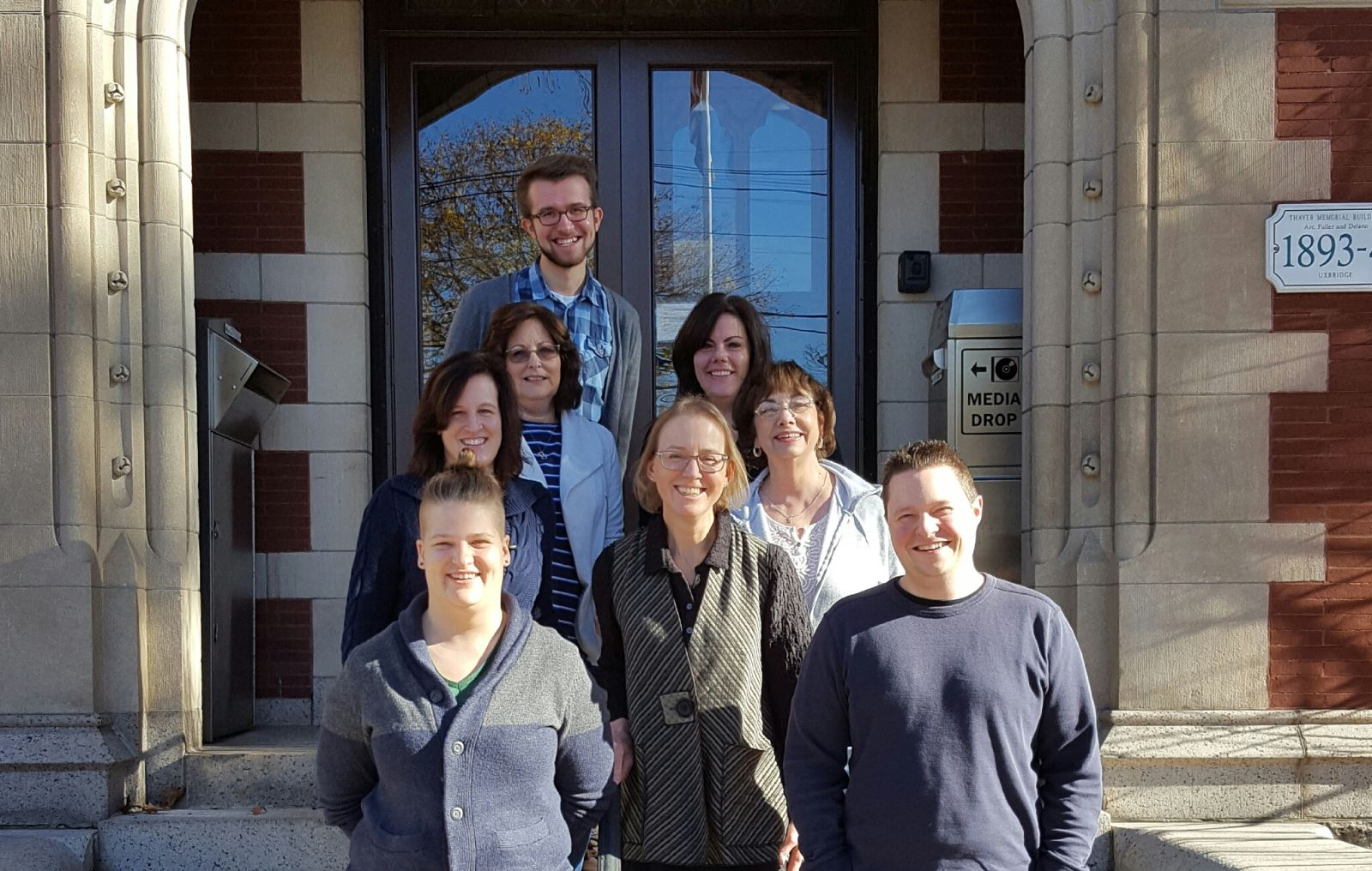 Staff photo of 8 staff members on the steps of the library